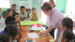 Bright room with mint green walls covered in learning posters. Young woman in lilac shirt writing at a desk surrounded by 17 children and 1 other young woman helper.