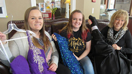 Two female students with dark blonde hair and one blonde woman sitting on a leather couch and holding up dresses that are purple, blue, and black.
