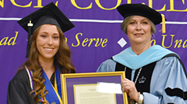 Ely King holding a framed award next to Defiance College President Richanne Mankey