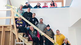 13 people standing on and above a stair case that is under construction. They are wearing hoodies and jackets of all colors and smiling at the camera.