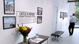 Large photos of scenes in the city of Defiance are hanging on the gallery wall. A table with flowers and a guestbook are sitting against the wall.