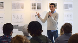 Student Federico Gutierrez holding a microphone and speaking in front of an audience who is watching him point at his design on the exhibit wall.