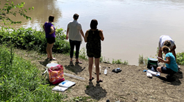 Five women standing near the Maumee river bank with equipment to test the water.