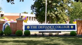 Purple and gold balloons around Defiance College sign