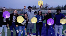 students holding purple and gold paper lanterns in the dark