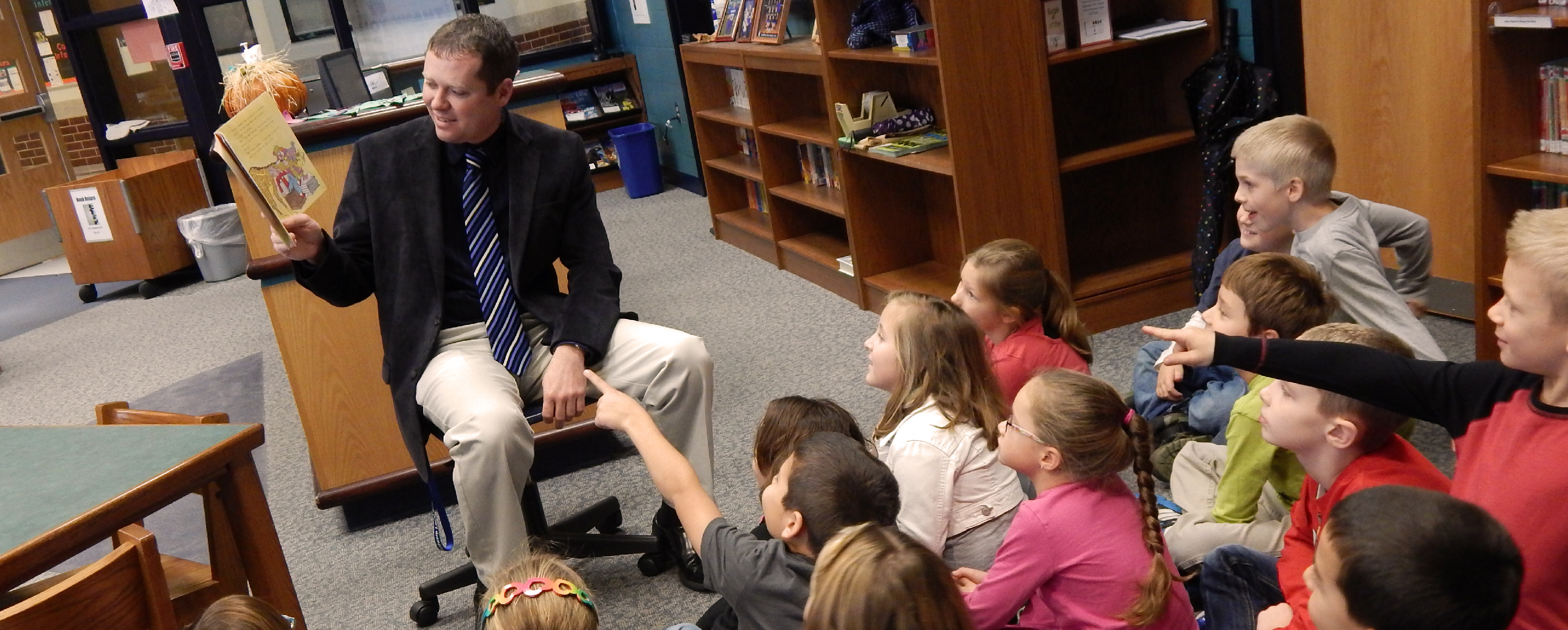 Man in business attire sitting on a chair with a book in front of a row of children who are pointing at the book and watching him share the book with excited expressions on their faces.