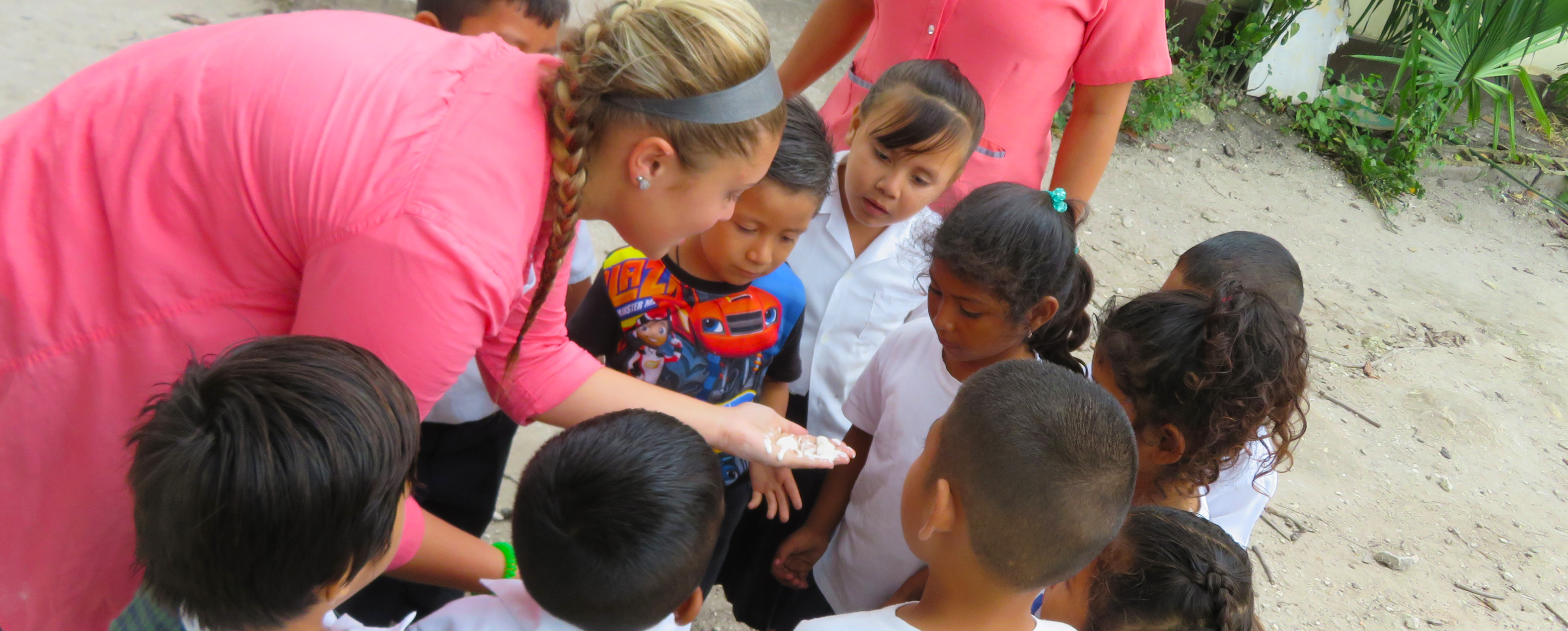 Blonde student surrounded by ten small children who are looking at a light colored substance on her palm which she is holding out.