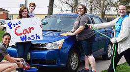 Five band members washing a blue car and holding a sign that says Free Car Wash