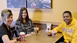 two admissions staff members with a student at a coffee house table