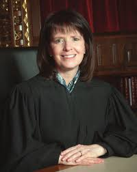 Ohio Supreme Court Justice French: woman with medium-length brown hair smiling at the camera and wearing black robes.