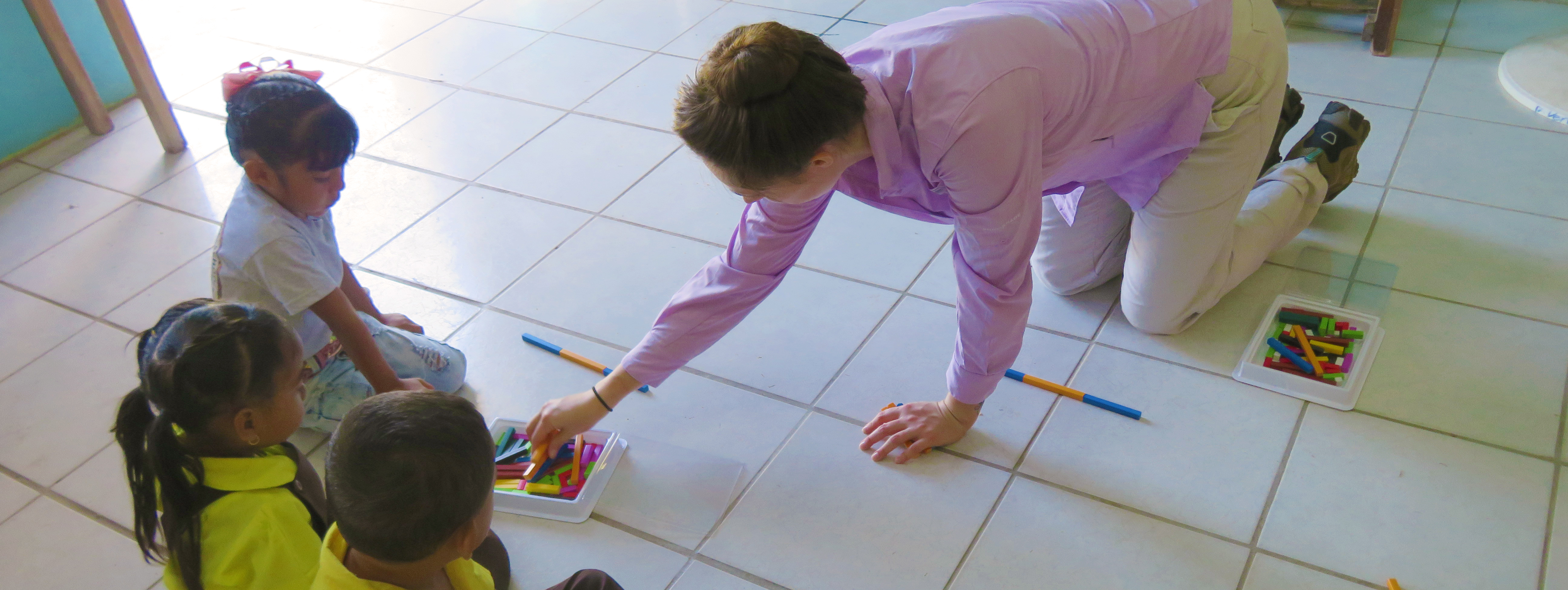 A young women with her hair pulled up in a bun is on her hands and knees on a while tile floor with three children. She is pulling colorful sticks from a plastic container on the floor.