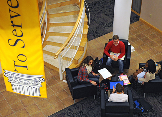 "Four students sitting on black leather chairs in a circle. A yellow banner is visible hanging from into the frame from the top saying ""to serve."""
